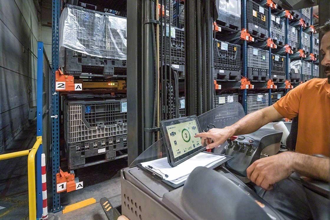 Un operario maneja el Pallet Shuttle desde el montacargas con una tableta digital